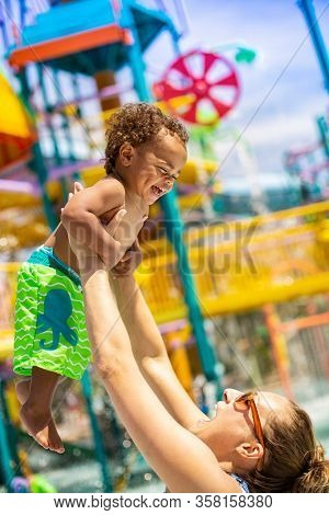 Little boy laughing with his mom at an outdoor water park during summer vacation. Smiling and having fun together. Cute, happy expression by a diverse bi-racial child in a vacation lifestyle photo.