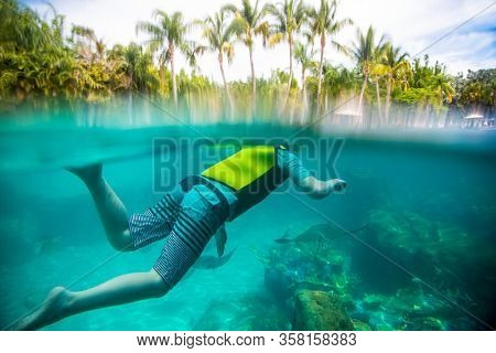 Underwater photo of Child snorkeling at a tropical resort. View from above and below the water level with stingrays swimming under the snorkeler