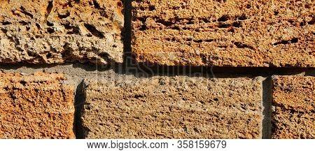 Brick Wall Of Yellow Shell Rock. Closeup Of Shellstone Texture. Background. Wide Photo