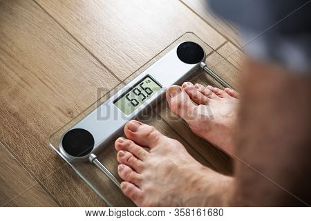 A Fit Man Standing On An Electronic Household Scale In A Bathroom. Weighing In Kilogram Scale.