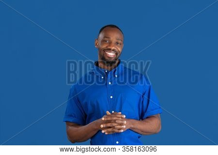 Smiling, Laughting. Monochrome Portrait Of Young African-american Man Isolated On Blue Studio Backgr