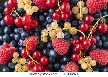 Background Of Fresh Berries And Fruits. Ripe Bilberries, Blueberries, Currants, And Raspberries. Mix
