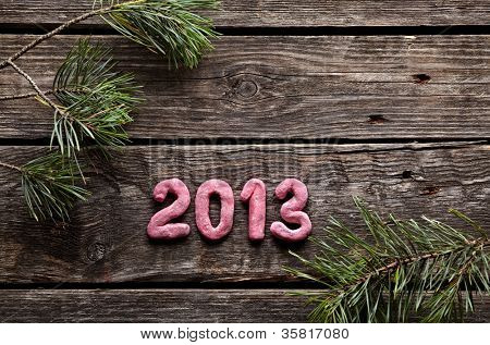 Numbers 2013 with spruce twigs on old wood. Sweet New Year holiday background.