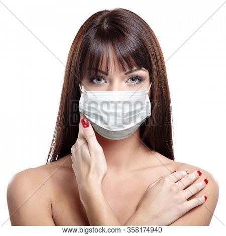 corona virus concept. happy young healthy woman puts on protective mask isolated on white background