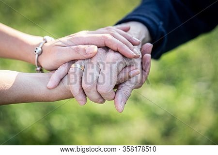 Caregiver, carer hand holding elder hand in hospice care. Philanthropy kindness to disabled concept.