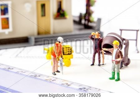 Closeup Of Small Miniature Plastic House With  Miniature Figurine Workers And Constructing Plans