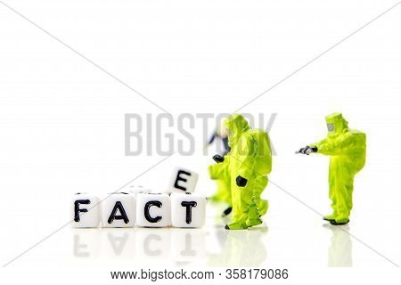 Fake And Fact Text Formed Of White Dices With Black Letters And Little Miniature Figurines Of Worker