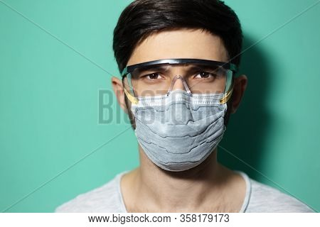 Studio Portrait Of Young Guy Wearing Medical Flu Mask And Safety Goggles, Coronavirus Prevention, Is