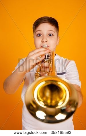 A Boy Plays The Trumpet. A Handsome Teenager Boy In A White T-shirt Plays Trumpet Musical Instrument