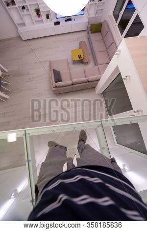 man standing upstairs on glass floor while looking at the inside of a stylish duplex apartment