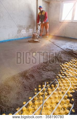 Laborer performing and polishing sand and cement screed floor on the construction site of a new two-level apartment. Sand and cement floor screed