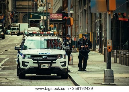 NEW YORK, USA - MARCH 21, 2020: Police in empty street with few pedestrians and traffic as the result of COVID-19 coronavirus pandemic outbreak in New York City.