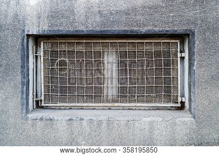Rectangular Basement Or Cellar Window Is Tightened With Wire Metal Mesh And Grille. Technical Floor