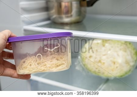 A Hand Taking Plastic Container With Leftovers From A Fridge.