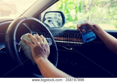 Hand Of Driver Is Spraying Alcohol To Car Steering Wheel To Kill The Coronavirus Covid19 Or Contamin