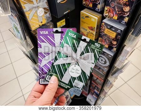 Montreal, Canada - March 22, 2020: Visa Gift Card In A Hand Over Gift Cards Background. Visa Is An A