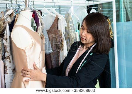 Asian Woman Dressmaker Fashion Designer Measuring Size Of Mannequin In Showroom. Concept Of Dressmak