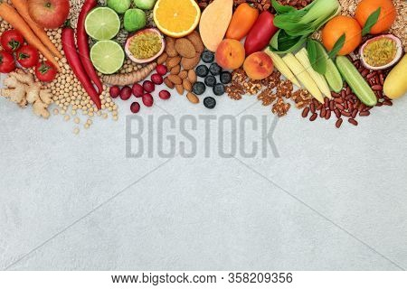Vegan health food background border with a foods to boost the immune system. High in protein, vitamins, minerals, antioxidants, anthocyanins, fibre, omega 3 and smart carbs. Ethical food concept.