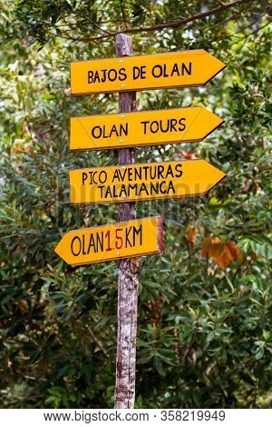 Olan, Costa Rica  - January 15 2020: Bright Yellow Sign In The Countryside With Directions To Tour G