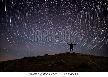 Night Landscape With A Contour Of A Man On Top Of The Hill In The Mountains Against A Starry Sky Wit