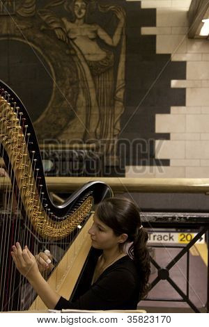 NEW YORK-JUL 28: Harpist Emily Hopkins performs in Penn Station on July 28, 2012 in New York, NY. She is on MTA'Â?Â?s official roster for the transit talent program called Music Under New York.