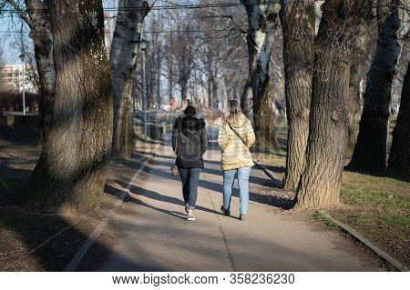 Two Women Walking On Street. Coronavirus Lifestyle. Rear View Of Women Walking In Park. People City