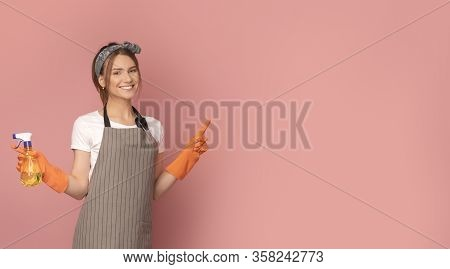Cleaning Concept. Smiling Young Woman In Apron Holding Detergent Sprayer And Pointing At Copy Space