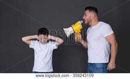 Family Abusement. Nervous Father Screaming At Son With Megaphone, Boy Closing Ears, Dark Studio Back