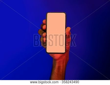 Mobile App. Male Hand Holding Smartphone With Blank Screen Advertising Application Over Blue Backgro