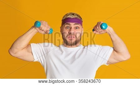 Funny Guy Is Engaged With Small Dumbbells, On Yellow Background, Free Space