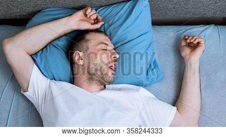 Coronavirus Quarantine Lifestyle. Man Sleeping Lying In Bed At Home During Pandemic Self-isolation.