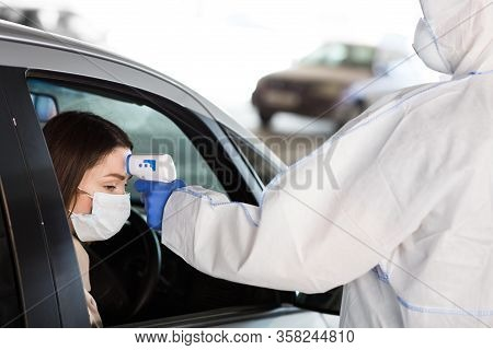 Medical Worker In Coronavirus Protective Suit Measuring Temperature Of Woman In A Car, Copy Space