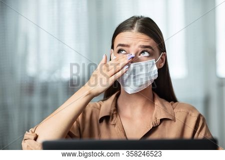 Dont Touch Your Face. Girl Wearing Surgical Mask Rubbing Her Eye With Dirty Hands, Working On Laptop