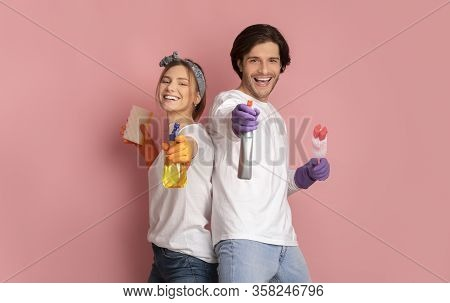 Housekeeping And Cleaning Service Concept. Smiling Young Couple Holding Spray Detergents, Standing O
