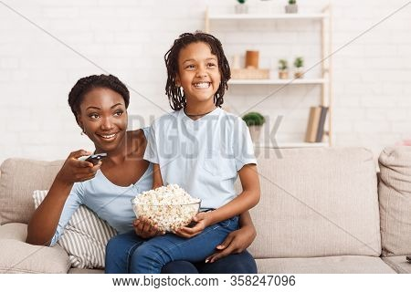 Family Time Concept. Happy African Mom And Child Sitting On Sofa, Eating Popcorn And Watching Tv, Em