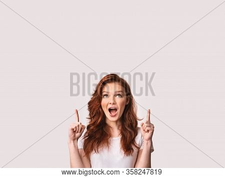 Look Up. Red-haired Teen Girl Pointing Fingers Upward At Free Space Posing Over White Background. St
