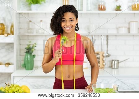 Dieting Concept. Smiling Black Girl With Measuring Tape Around Her Neck Eating Fresh Vegetable Salad