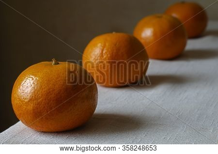 Tangerines On The Table. Line Of Tangerines On A Light Table. Four Ripe Tangerines In A Row Close-up