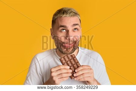 Enjoy Sweet. Funny Guy Is Smeared, Eats Chocolate And Rolls His Eyes