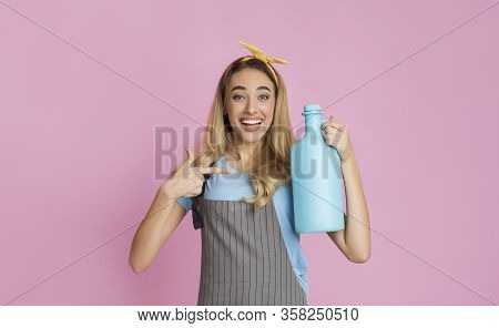 Smiling Housewife Points Finger At Fabric Softener, On Pink Background, Empty Space