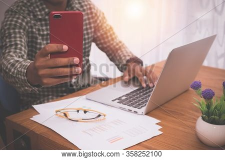 Businessman Using Mobile  Take A Photo And Using Laptop In Office Room.