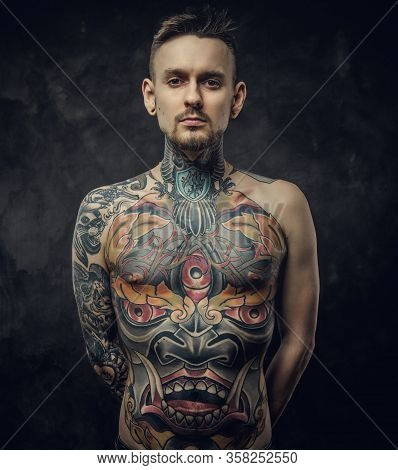 Confident Tattoo Artist Posing In A Dark Studio With A Half-naked Body Wearing Jeans, Tattooed In A