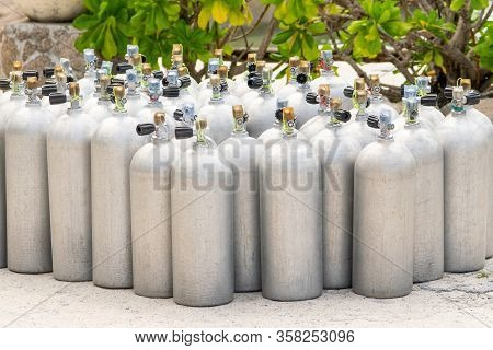 A Lot Of Aluminum Scuba Diving Oxygen Tanks Standing In Front Of The Green Beach Bushes And Rocks On