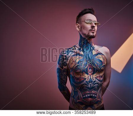 Assertive Male Model Posing In A Neon Studio With A Half-naked Body Wearing Sunglasses And Tattooed