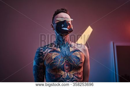 Bold And Rebellious Male Model Posing In A Neon Studio Wearing A Medical Mask On His Face, Yellow Su