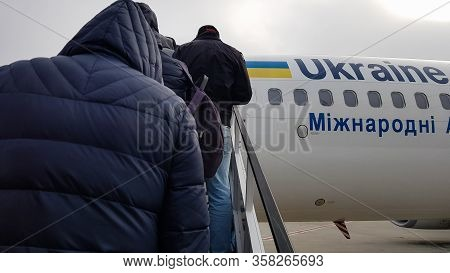 Ukraine, Borispol - March 27, 2020: Unidentified Tourists People Climb On A Plane. Passengers Go In