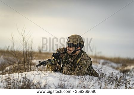 Modern War Soldier Army Man In Multicam Camouflage Is Lying And Speaks On The Walkie-talkie Radio. F