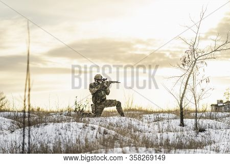 Modern Special Forces Soldier On Combat Mission. Open Fire Area Field. Skirmish With Commandos