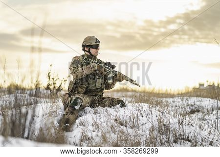 Modern Soldier In Multicam Camouflage Is Lying And Aiming Aim At The Sight. Full Equipment Commandos