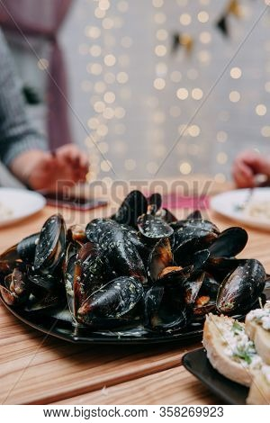 Raw Mussels On A Black Plate At A Cooking Class. Master Class On Seafood. Cooking Mussels. Close-up,